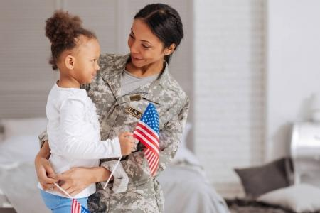 child and her mom holding little flags