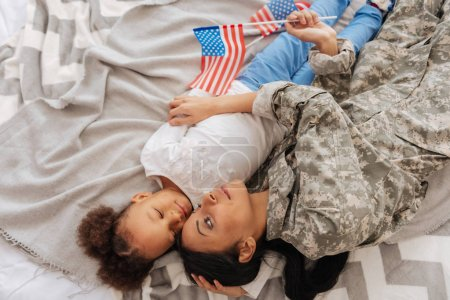 child and her mom resting in bed