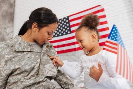 girl examining her mothers uniform