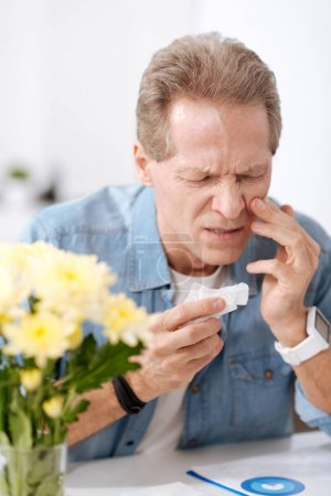 Disturbed man having allergy on flowers