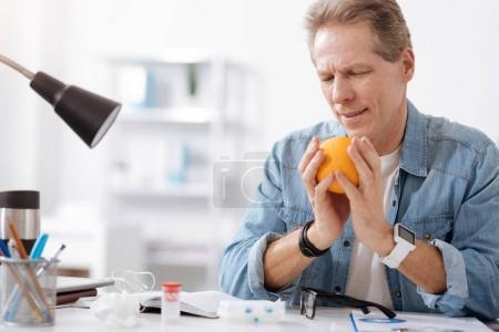 Smiling man holding tasty orange