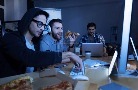 Cheerful delighted man eating pizza