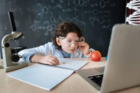 Hardworking little researcher doing homework in the laboratory