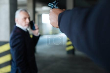 Selective focus of a handgun directed at the businessman