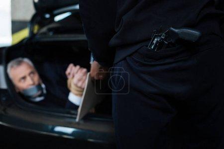 Selective focus of a handgun being behind criminals back