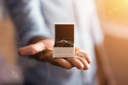 Young African American homme démontrant la bague de fiançailles