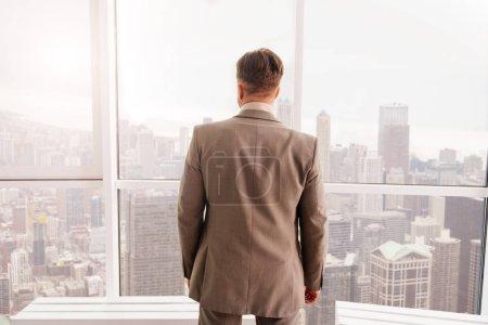 businessman standing near window