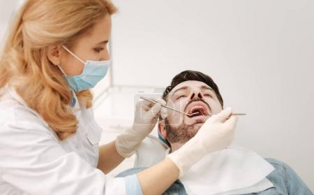 Productive talented dentist conducting a dental cleaning