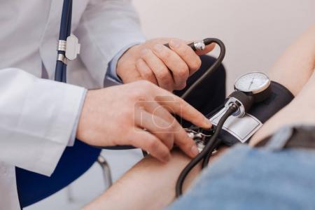 Nice careful medical worker employing a blood pressure sensor