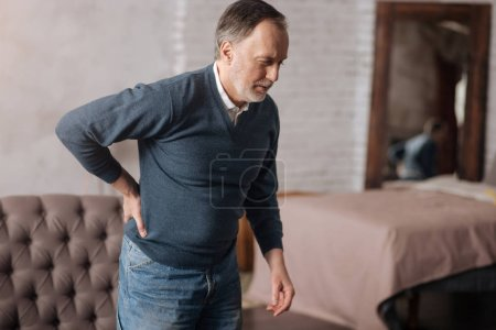 Old man standing with pain in back
