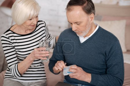 Old man going to take pills near his wife