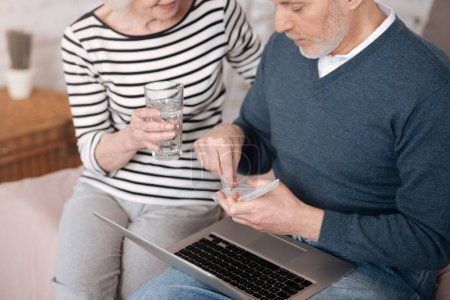 Top view of senior couple going to take pills