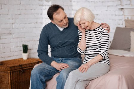 Man giving solace to his elderly crying wife