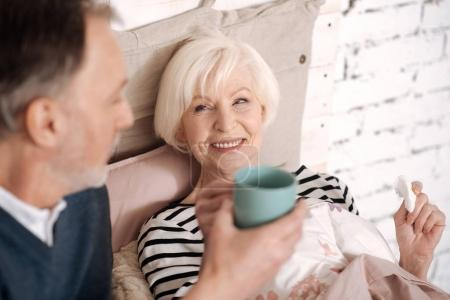 Closeup of senior lady taking tea from her husband