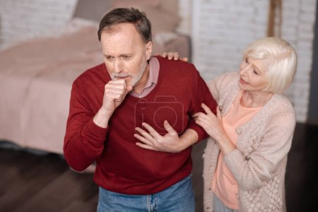 Aged man coughing near his wife