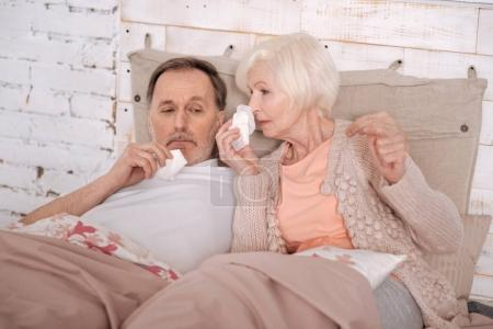 Elderly couple lying on bed with cold