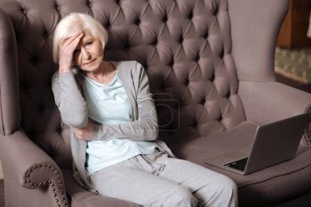 Elderly woman sitting with headache