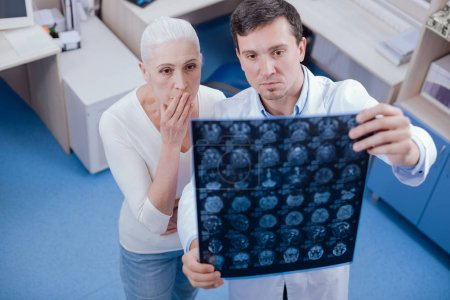 Serious shocked woman looking at her brain X ray images
