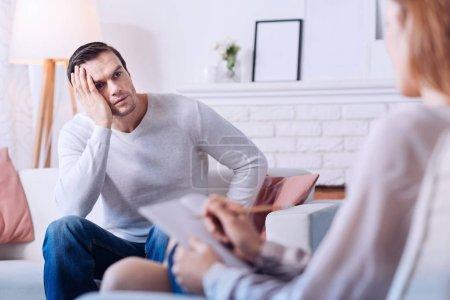 Sad depressed man looking at his psychologist