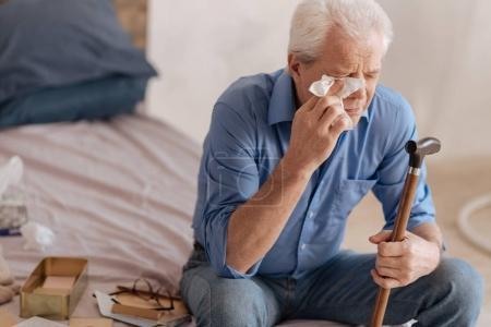 Depressed gloomy man wiping away his tears
