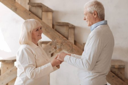 Cheerful elderly couple holding hands together