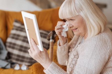 Sad crying woman wiping away her tears