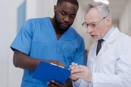 Photo pour Demander un collègue expérimenté. Jeune médecin afro-américain travailleur permanent à l'hôpital tout en tenue de dossier et l'écoute de l'opinion de la collègue de vieillissement - image libre de droit