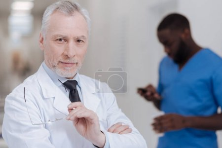 Cheerful aged physician expressing positivity at work