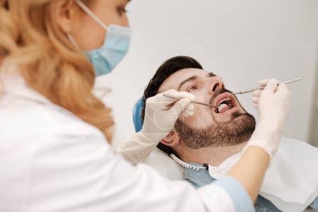 Stressed gentleman having his teeth checked