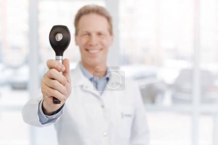 Cheerful medical specialist demonstrating dermatoscope in the clinic
