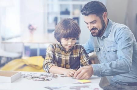 Photo for Good family times. Smiling father tagging along smart son while playing with puzzle and enjoying leisure time together - Royalty Free Image
