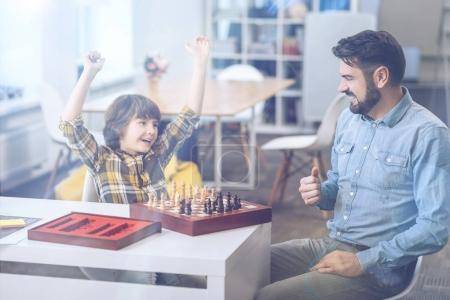 Excited little boy celebrating his chess win