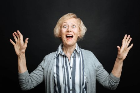 Amused aging woman expressing emotions in the studio