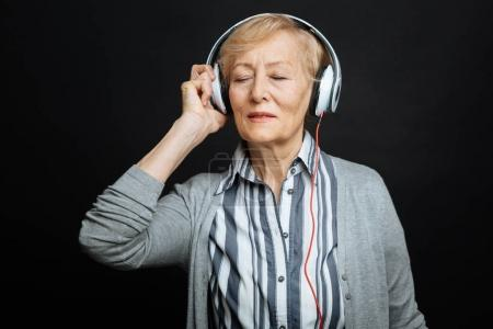 Peaceful pensioner enjoying music in the black colored studio