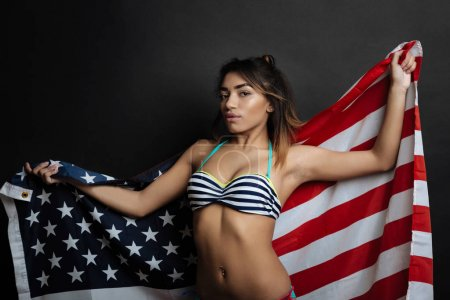 Cheeky Hispanic American woman holding American flag indoors
