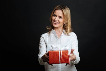 Smiling young woman presenting gift box in the studio