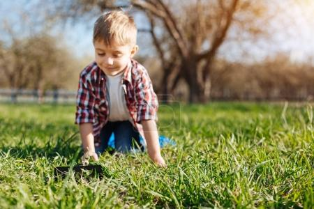 Cheerful boy crawling on hands and knees in backyard