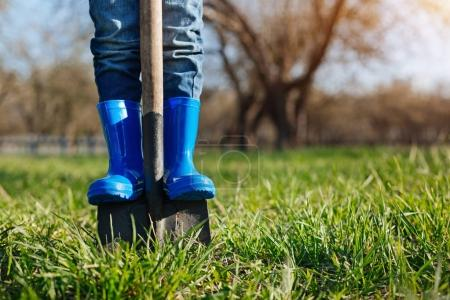 Close up of childs feet in rubber boots on shovel