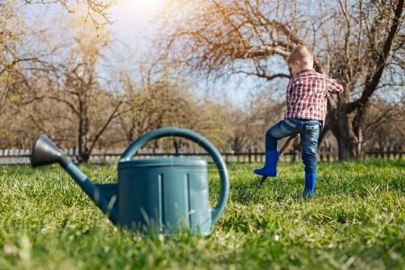 Little boy wearing blue wellies digging in garden
