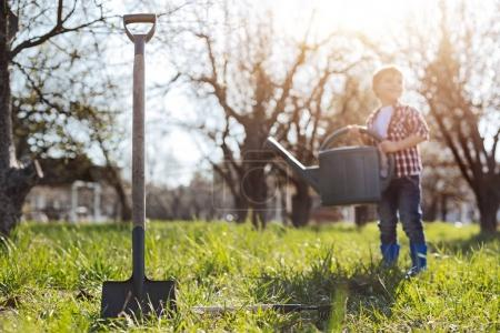 Charming kid holding watering can in garden