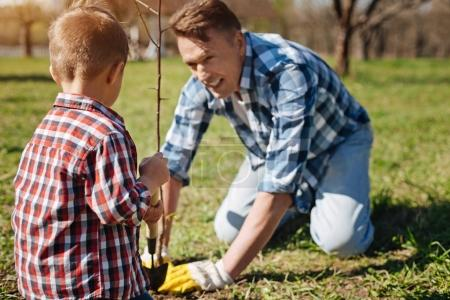 Father and son scooping soil in garden