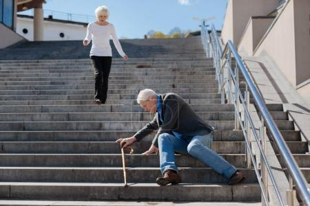 Disappointed pensioner sitting on stairs in the street