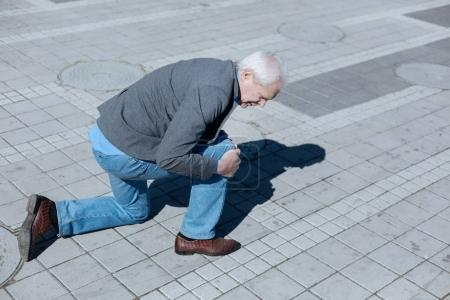 Aged pensioner falling on the ground in the street