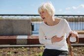 Unhappy woman enduring heart attack near the river