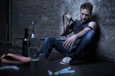 Apathetic addict tying tourniquet in the dark basement