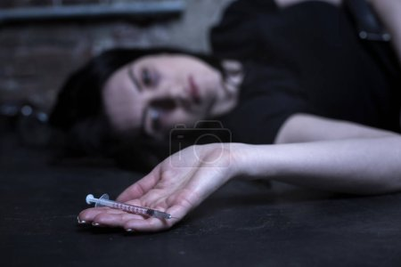 Exhausted drug addict lying on the ground