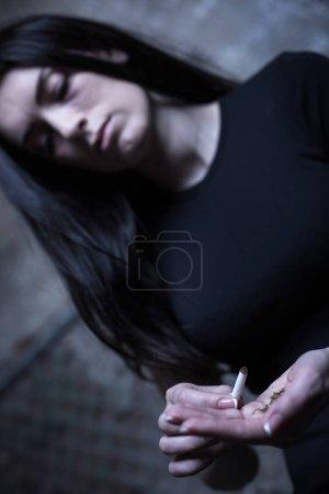 Indifferent drug addict using marijuana cigarette outdoors