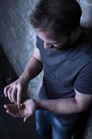 Homeless man holding marijuana cigarette in the dark corner