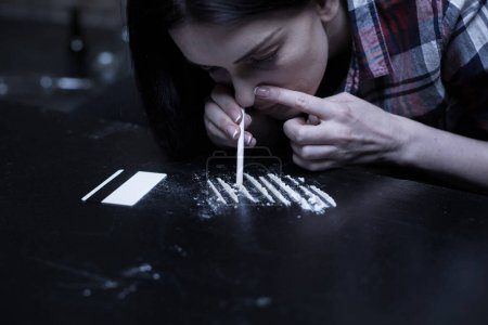 Drug addict snorting heroin lines in the dark place