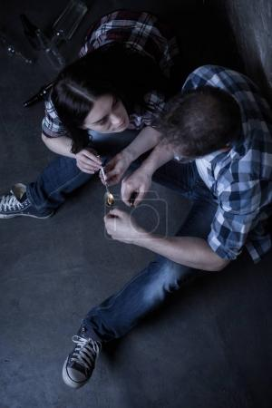 Exhausted junkies preparing cocaine over the flame in the darkness